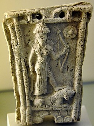 Goddess_Ishtar_stands_on_a_lion_and_holds_a_bow,_god_Shamash_symbol_at_the_upper_right_corner,_from_Southern_Mesopotamia,_Iraq.jpg